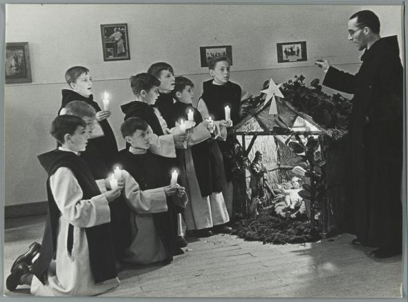 A Monk conducts a Christmas choir of boys dressed in religious robes to sing Christmas carols beside a nativity display. Bruges, 1935 Courtesy Flickr Commons